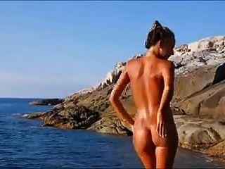 rubia desnuda playa caliente posando en las rocas