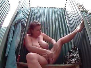 Mujer madura con grandes tetas toma una ducha sexy.