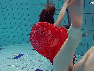 Adolescente vestida de rojo nadando con los ojos abiertos.