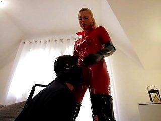 puta en traje de látex rojo gato botas negras folla esclavo