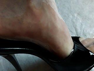 Pies en medias de nylon y tacones altos empapados en orina