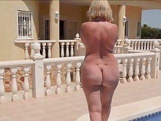 Una mujer madura con un culo redondo desnudo camina por la piscina.